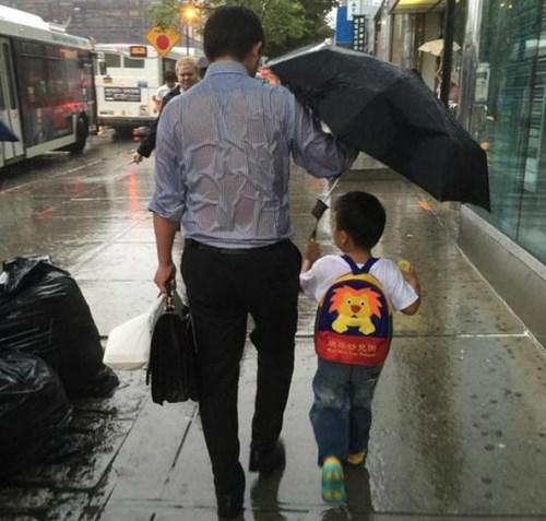 Bức ảnh ông bố che ô cho con khiến hàng triệu trái tim của cư dân mạng xúc động. (Ảnh:Internet)