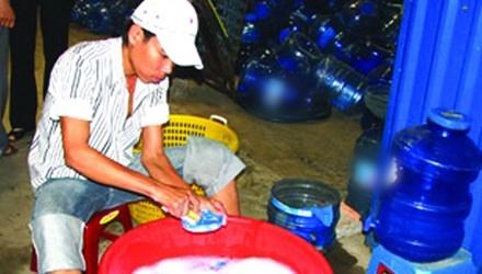 Xúc rửa bình qua loa bằng nước rửa bát. Ảnh: Lê Nguyễn