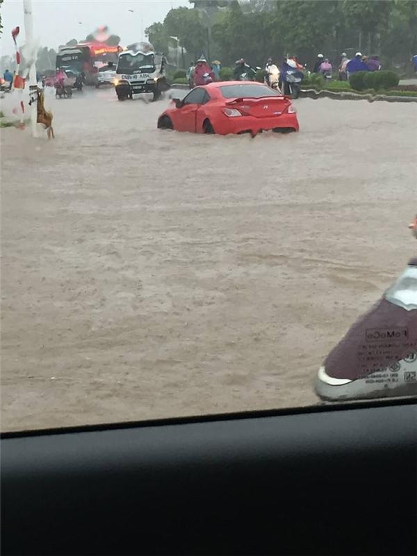 Ô tô cũng chịu trận, không thể làm gì hơn trước dòng nước ngập cao(Ảnh: FB)