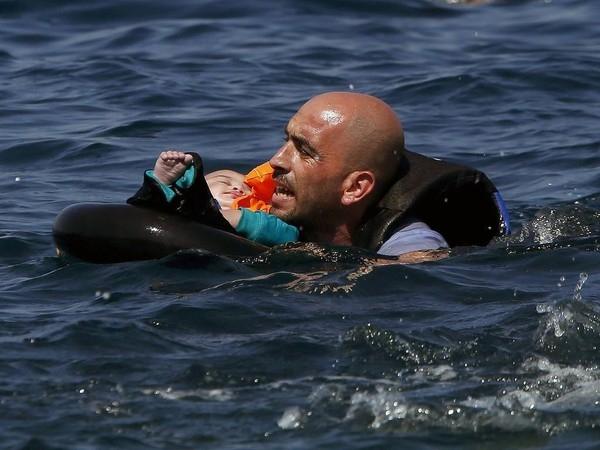 Bức ảnh kể về câu chuyện của một người đàn ông Syria đãđặt con lên xuồng cao su chở người tị nạn, chiếc phao đã bị xì hơi khi mà nó sắp cập bờ biển Hi Lạp 100m.Và hình ảnh này tượng trưng cho những nguy hiểm mà những người tị nạn phải đối mặt.(Ảnh Internet)