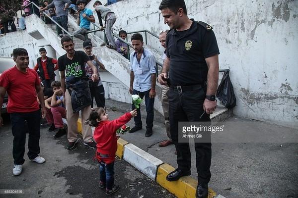 Một hình ảnh rất đẹp của một cô bé trong đoàn người tị nạn tặng một bông hoa cho người cảnh sát Thổ Nhĩ Kỳ đang làm nhiệm vụ trấn át dân tị nạn biểu tình. Con số người tị nạn không có đồ ăn, thức uống và mắc phải những bệnh dịch nguy hiểm đã lên đến hàng nghìn người, khi mà chính phủ Thổ Nhĩ Kỳ không cho phép bán vé xe bus tới biên giới khiến họ phải chờ đợi rất nhiều ngày tại nhà ga trong vô vọng.(Ảnh Internet)