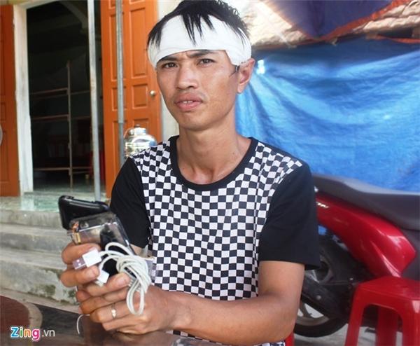 Anh Quân cầm trên tay chiếc iPhone 3 bị vỡ vụn. Ảnh: Phạm Hòa.