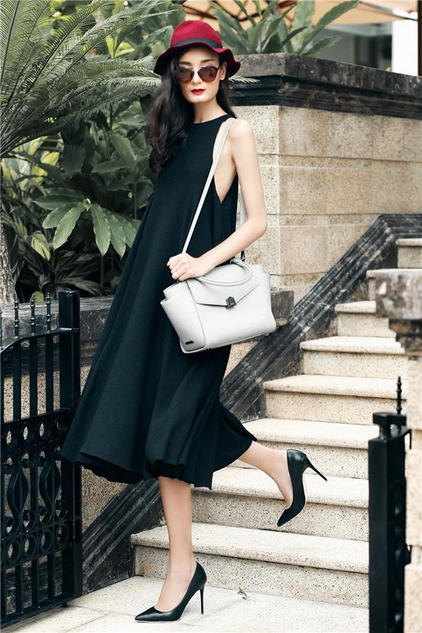 Lê Thúy diện bộ váy cùng túi đeo tông xám trắng, mũ fedora màu đỏ rượu cùng mắt kính trẻ trung.