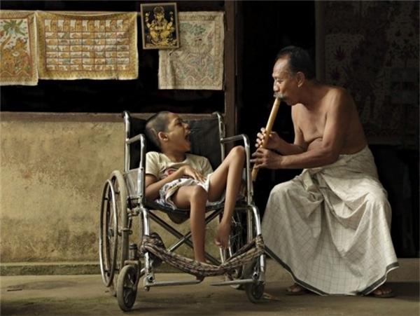 Bali: Người đàn ông thổi sáo bên cạnh cậu bé tàn tật mà ông yêu quý như đứa con ruột thịt.