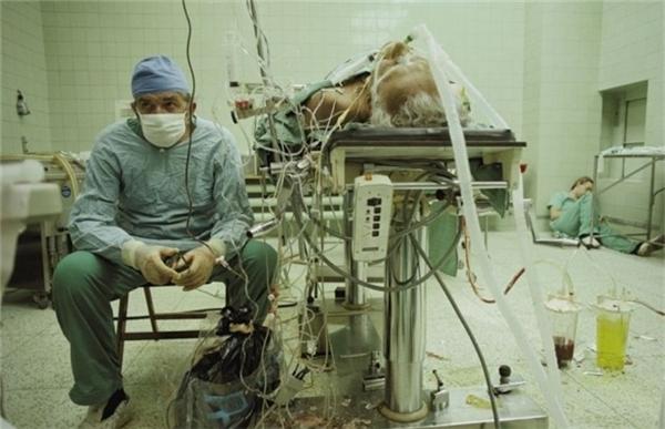 Một bác sĩ phẫu thuật ngồi kiệt sức sau ca cấy ghép tim thành công suốt 23 giờ. Cô trợ lý của ông ngủ mê mệt trong góc phòng.
