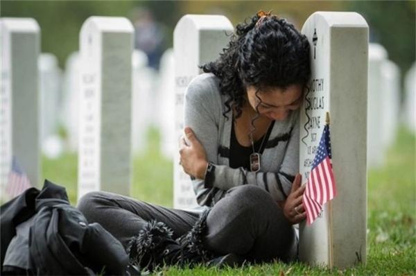 Người phụ nữ ngồi khóc bên mộ chồng một ngày trước lễ kỷ niệm ngày cưới.