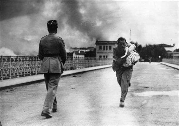 Một nhà báo ôm một đứa trẻ chạy qua cây cầu trong cuộc nội chiến năm 1936 Tây Ban Nha.
