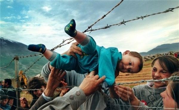 Kosovo: Một cậu bé được đưa qua hàng rào thép gai của trại tị nạn cho ông bà của mình.