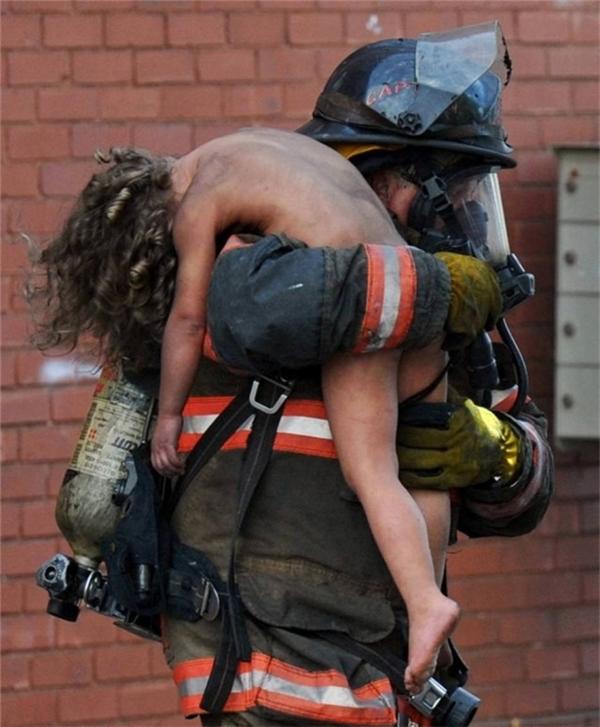Người lính cứu hỏa đang cứu cô gái nhỏ người Mỹ