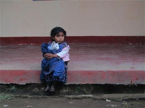Một bé gái Guatemala ôm chú mèo của mình.