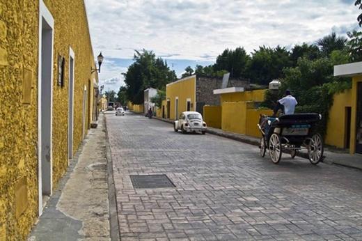 """Izamal, Mexico: Chính thức được tuyên bố là """"Thành phố ma thuật"""" luôn ngập tràn màu nắng với những ngôi nhà sơn màu vàng. Thành phố mang lại cảm giác ấm áp trong mọi điều kiện thời tiết. Những con đường đá cuội nối liền các nhà thờ bằng đá vôi và các tòa nhà chính phủ. Nhà thờ San Antonio de Padua từ thế kỷ 16 thu hút khách thập phương bởi những câu chuyện lịch sử và thần thoại."""