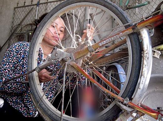 Nghề sửa xe đạp giúp chị nuôi con khôn lớn. Ảnh: Đức Hùng