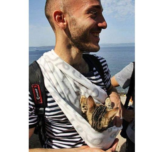 Người đàn ông nâng niu con mèo nhỏ trước ngực khi đặt chân tới đảo Lesbos, Hy Lạp.
