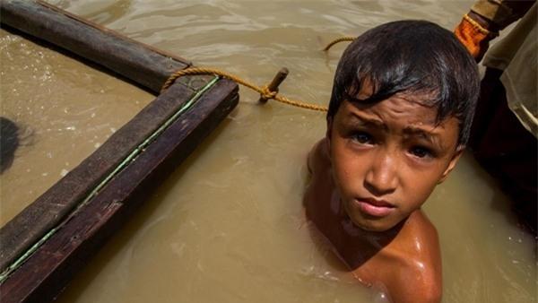 Một em bé 11 tuổi phải lặn xuống nước để tìm vàng