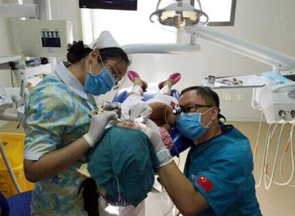 Hình ảnh bác sĩ quỳ gối suốt 40 để thực hiện ca phẫu thuật cho bé gái đã nhận được hưởngứng mãnh liệt từ cộng đồng mạng. (Ảnh Internet)