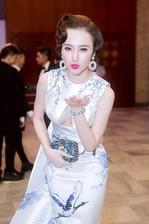 Angela Phương Trinh cũng từng gây ấn tượng mạnh khi diện bộ váy có họa tiết rồng phượng, chim hạc tông xanh lam theo phong cách cổ điển với mái tóc xoăn nhẹ.