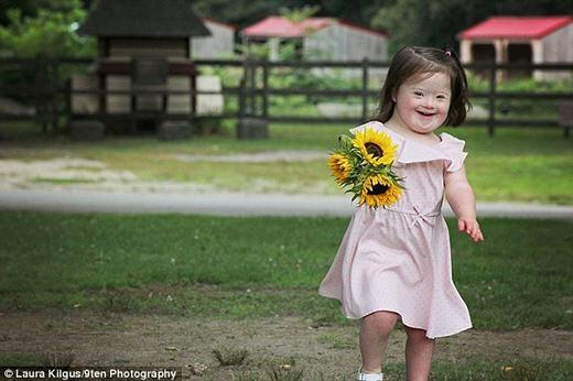 Một em bé bị Down đang cười rất tươi, trên tay là bó hoa vừa được tặng. (Ảnh:Laura Kilgus)