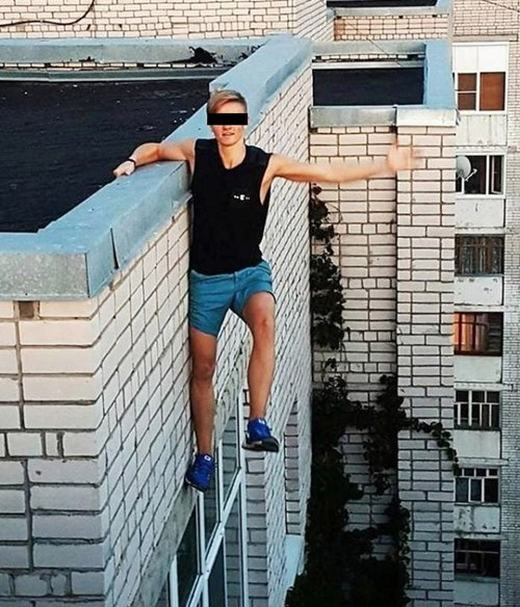 """Đầu tháng này, một nam sinh 17 tuổi người Nga đã chết vìchụp ảnh """"tự sướng"""" trên một tòa nhà cao 9 tầng. Khi leo được đến nơi cao nhất và chuẩn bị cho cảnh chụp thả người, dây an toànbị tuột khiến anh rơixuống đất. Dù vẫncòn sống khi tiếp đấtnhưng chàng trai người Nga nàyđã chết trên đường tới bệnh viện do vết thương quá nặng. Được biết, nạn nhân có sở thích chụp """"tự sướng"""" ở những địa điểm nguy hiểm như núi cao, tòa nhà, đỉnh cầu… (Ảnh: Internet)"""