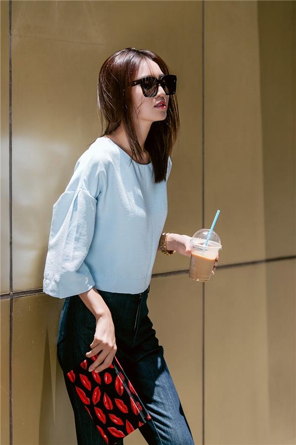 Hình ảnh của người phụ nữ hiện đại, trẻ trung được cô nàng diễn viên xinh đẹp khắc họa chân thực qua chiếc quần jeans cạp cao phối cùng áo phom rộng có tông xanh thiên thanh dịu mát. Chiếc ví hộp cầm tay có họa tiết đôi môi đỏ càng làm tăng thêm sức hút cho tổng thể.