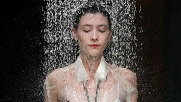 Ngay sau đó, nước từ hai vòi trên cao bất ngờ ập xuống làm ướt cả lớp áo bên ngoài được làm bằng giấy. Sau đó, lớp trang phục bên trong dần được hiện ra với cấu trúc cùng họa tiết khá đặc biệt, lạ mắt.