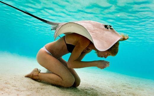 """Một cô gái """"đội"""" trên đầu chú cá đuối. Bức ảnh được chụp ở ngoài khơi bờ biển Tahiti. (Ảnh: Smartshot)"""