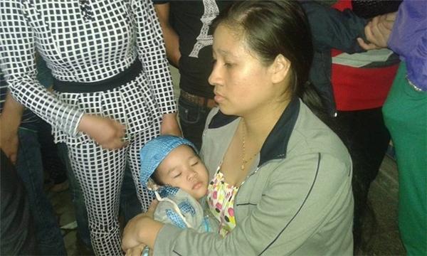 Người mẹ bế con nhỏ được giải cứu khỏi toà nhà. Cháu bé mệt ngủ thiếp đi trong vòng tay mẹ sau biến cố hoảng loạn. Ảnh: Dân Trí