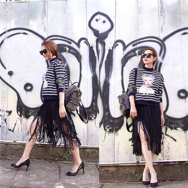 Một trong những bộ trang phục đầy thu hút không thể bỏ qua của Minh Hằng trong thời gian gần đây chính là sự kết hợp giữa chiếc áo phông kẻ sọc in họa tiết cùng chân váy tua rua điệu đà.