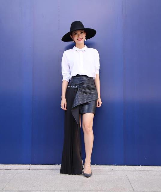 Áo sơ mi trắng kết hợp cùng chân váy midi có cấu trúc bất đối xứng hiện đại.