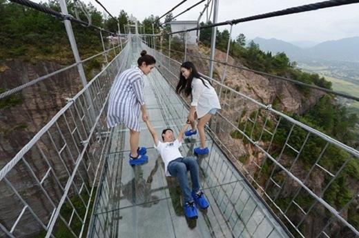 """Đây là cây cầu kính dài nhất thế giới (300 m) ở độ cao 180 m tại công viên địa chất Hồ Nam (Trung Quốc) được các kỹ sư làm việc liên tục 12 tiếng mỗi ngày để thay thế lớp gỗ bằng kính trong suốt.Nơi đây thu hút nhiều bạn trẻ đến tham quan và trải nghiệm đường đi """"lên trời"""" này."""