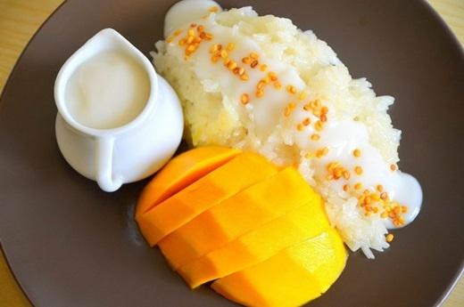 """""""Nhập cư"""" từ người hàng xóm Thái Lan, xôi xoài đang dần trở nên phổ biến và được nhiều người Sài Gòn yêu mến vì phần xôi dẻo, ngọt tự nhiên, xoài chín thơm """"không đỡ nổi"""" và có màu vàng bắt mắt cùng nước xốt dừa vừa bùi vừa béo.(Nguồn: Internet)"""