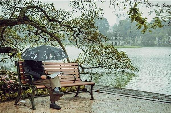 Buổi sáng trời mưa nhẹcùngchiếc ô nhỏ và tờ báo, nơi gócbờ hồ... cuộc sống dung dị của người dân Thủ đô.(Ảnh: Instagram)