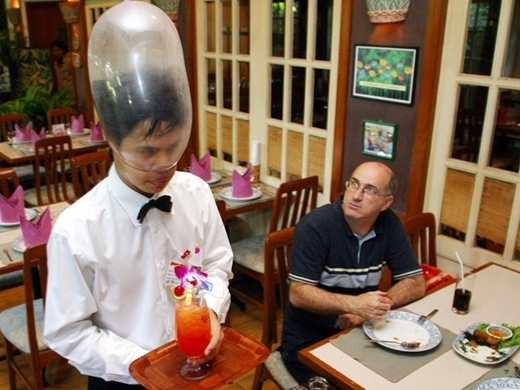 Một bồi bàn người Thái đeo chiếc bao cao su trên đầu khi phục vụ đồ uống tại nhà hàng Cabbages and Condoms ở Bangkok, Thái Lan. Mục đích của nhà hàng là giáo dục cho cộng đồng về tình dục an toàn.