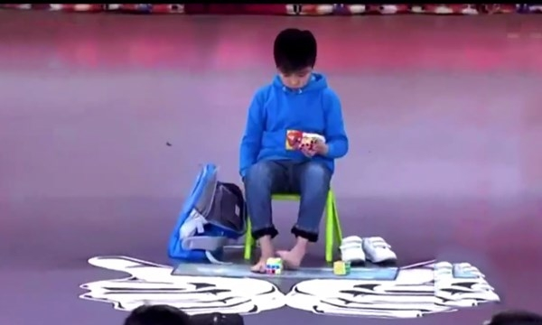 Jianyusử dụngcả tay và chân để giải rubik. (Nguồn: Internet)
