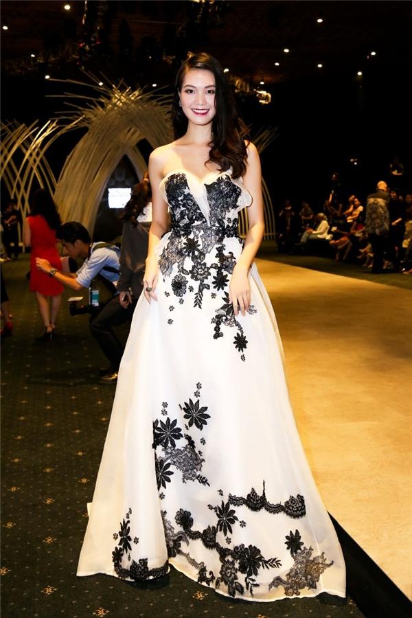 Thùy Dung diện chiếc váy trắng cúp ngực bồng xòe của nhà thiết kế Hoàng Hải. Thiết kế có phom cổ điển được tạo điểm nhấn họa tiết ren đen đính kết tương phản.