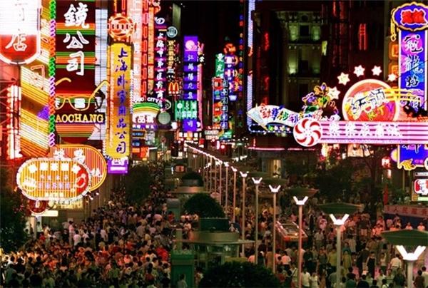 Người dân đi mua sắm dưới ánh đèn neon rực rỡ trên 1 con phố đông đúc ở Thượng Hải.