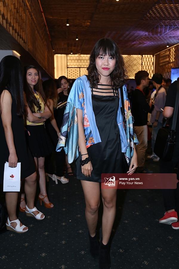 Nữ khán giả khoe chân dài trong chiếc đầm đen ngắn kết hợp áo khoác tông xanh bên ngoài.