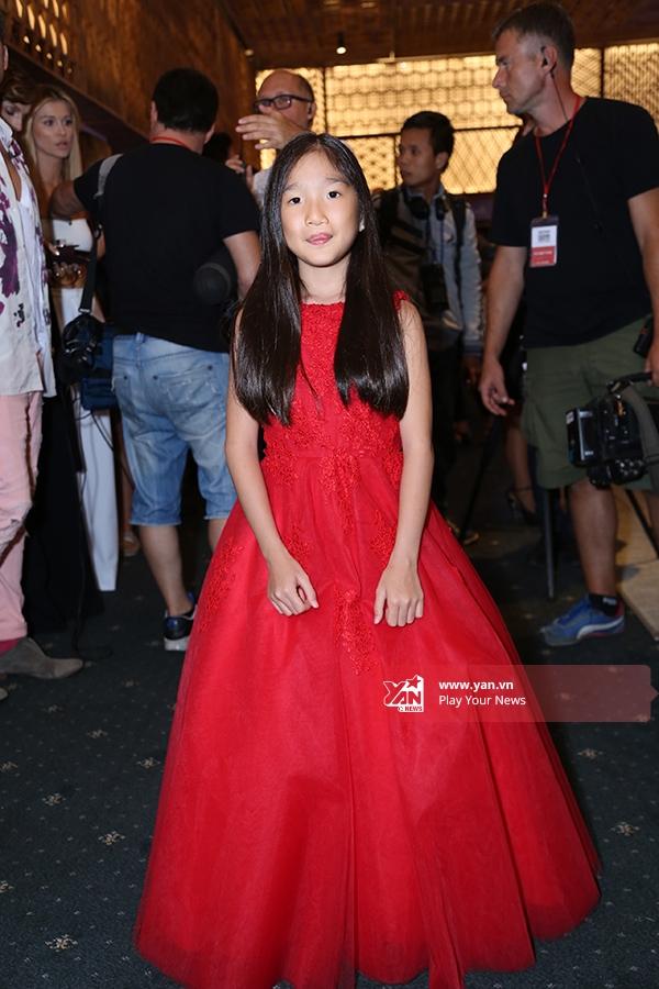 Một cô bé điệu đà trong chiếc đầm xòe tông đỏ nổi bật.