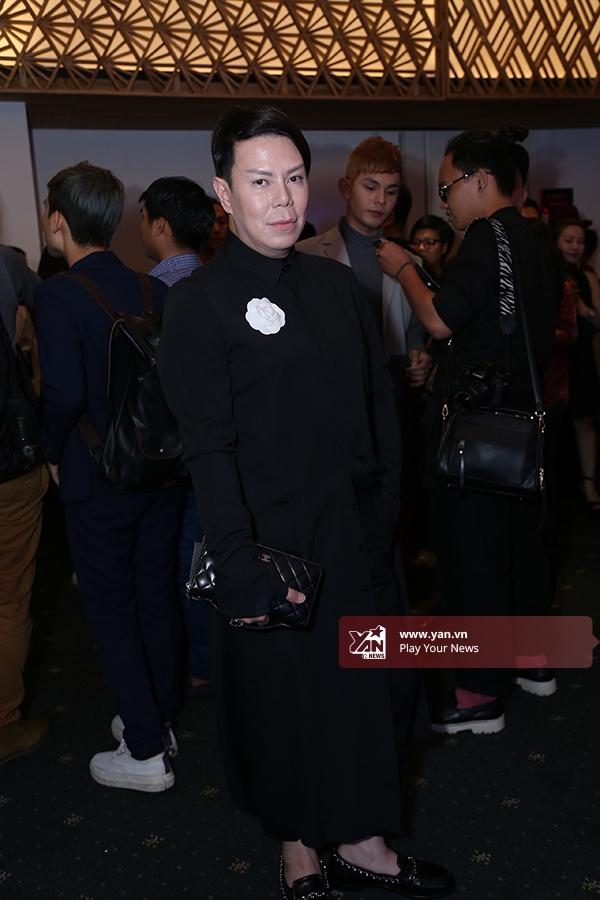Một vị khách tham dự buổi biểu diễn trong bộ váy đen điểm xuyết cài áo hoa hồng trắng tinh khôi.