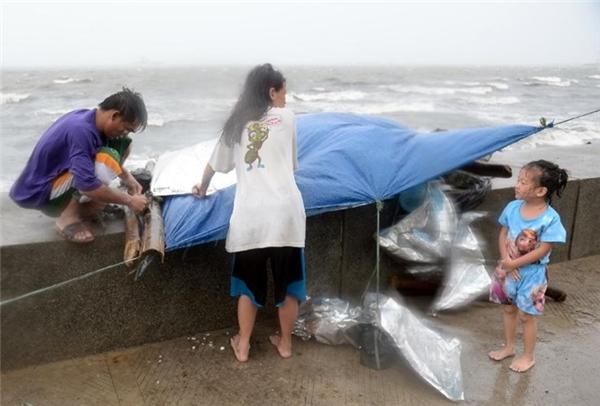 Một gia đình nhỏ cố gắng buộc và chấp vá lại căn lều tạm của mình trước những cơn gió dữ tợn do siêu bão Koppu gây ra. Ảnh: Internet