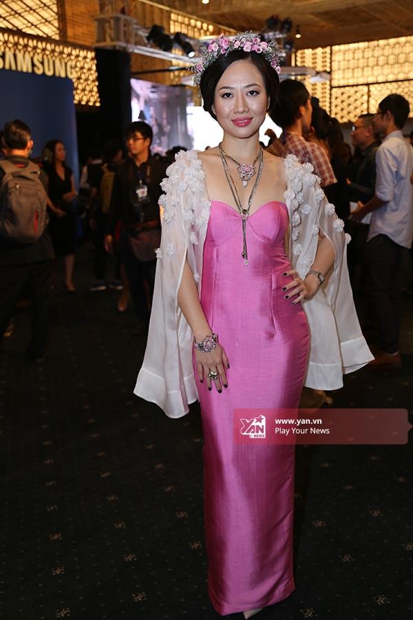 Nhà thiết kế Các Lâmlựa chọn cho mình tạo hình trẻ trung với chiếc váy hồng ôm sát kết hợp áo khoác đính kết bên ngoài. Vòng hoa trên đầucàng làm tăng thêm sự thu hút cho tổng thể.