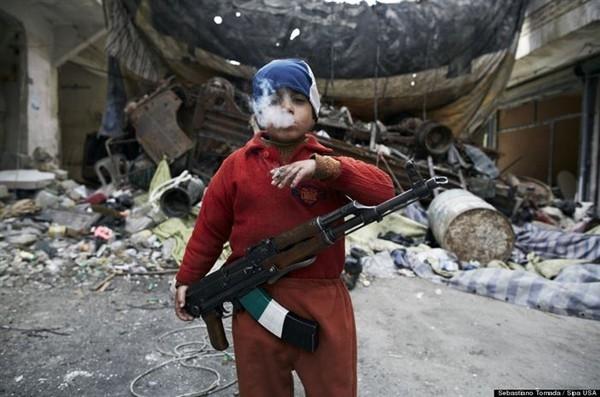 Đôi mắt của một tuổi thơ bị đánh cắp- Trong ảnh là một chiến binh phe nổi loạn tại Syria. Em mới chỉ 8 tuổi nhưng đã biết cầm súng AK47 và hút thuốc lá. Sâu thẳm trong mắt em có lẽ là sự gào thét của một đứa trẻ bị tước đi những tháng ngày ngây ngô nhất.