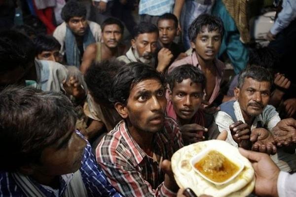 Đôi mắt cầu xin- Một nhóm những người vô gia cư đang giơ tay đón nhận phần thức ăn miễn phí của một tổ chức nhân đạo tại New Delhi, Ấn Độ.