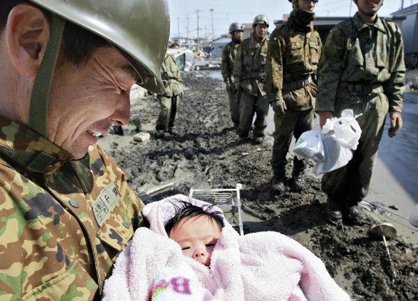 Sau bao ngàyròng rã kiếm tìm từ đống đổ nát khi cơn sóng thần tàn bạo càn quétxứ Phù Tang, viên cứu hộ đã mỉm cười hạnh phúc vìcứu sống được đứa bé 4 tháng tuổi một cách thần kì.(Ảnh: Internet)