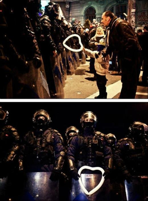 Trong cuộc biểu tình tại Bucharest, đứa trẻ Rumani đã tặng chiếc bong bóng hình trái tim cho một viên cảnh sát chống bạo động. Khoảnh khắc này đã khiến người chứng kiến rùng mình vì xúc động. Sĩ quan cảnh sát đã chân thànhđón nhận món quà, như một minh chứng cho sợi dây kết nối tình cảm ấm áp giữacon người trong thế giới đầy biến động.(Ảnh: Internet)
