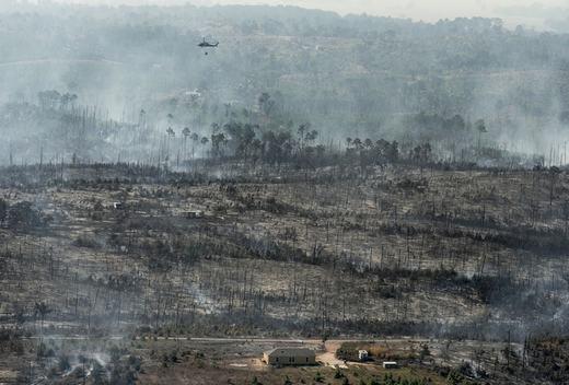 Chiếc máy bay trực thăng đang phun nước trong vụ cháy rừng ở Hidden Pines, Texas, Mỹ. (Ảnh: Rodolfo Gonzalez)