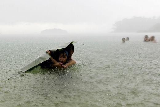 Người đàn ông mạnh mẽ đang che chở cho con gái bằng tàu lá chuối trong trận lụt ở Colon City, Panama. (Ảnh: Carlos Jasso)