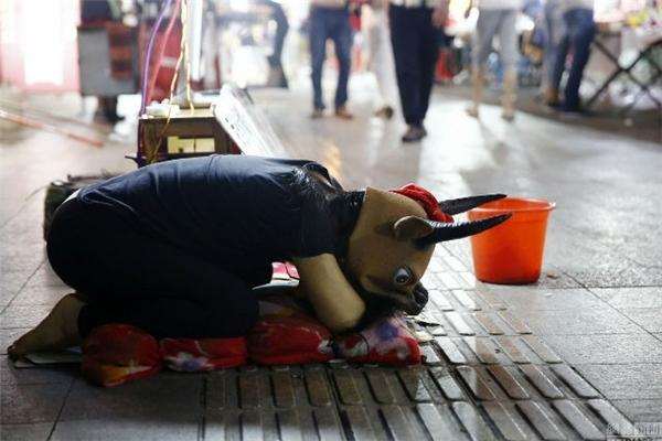 """Cách đây không lâu, hình ảnh một cô gái người Trung Quốc đeo mặt nạ trâu, quỳ lạy ngoài đườngxin được """"làm trâu làm bò"""", chỉ mong có tiền để chữa bệnh cho cha đã thật sự gây ấn tượng mạnh. Được biết, cô gái tên là Hao Dongdong,15 tuổi ở An Huy,Trung Quốc. Cha cô bé bị gãy cổ do chấn thương, hiện đã bịbại liệt.Mỗi tháng, cha cô phải cần 5.000 nhân dân tệ (hơn 17,5 triệu đồng)để chữa bệnh, trong khi đó cô còn haingười em nhỏ cần nuôi ăn học.Người mẹ vìkhông chịu đượcáp lực cuộc sống đã bỏ lạichồng con và ra đi. Cũng có những ngày,Haođưa bố theo để mọi người tin rằng cô không nói dối, cũng nhưsẵn sàng làmbò để mọi người cưỡi, chỉ mong mỗi người hãy cho cô xin 5 tệ (khoảng 17,500 đồng)để có thể chữa trị cho cha. Hình ảnh cô con gái nhỏ hiếu thảo, gồng mình cứu cha, nuôi gia đìnhkhiến cho cộng đồng mạng phải rơi nước mắt xúc động.(Ảnh: Internet)"""