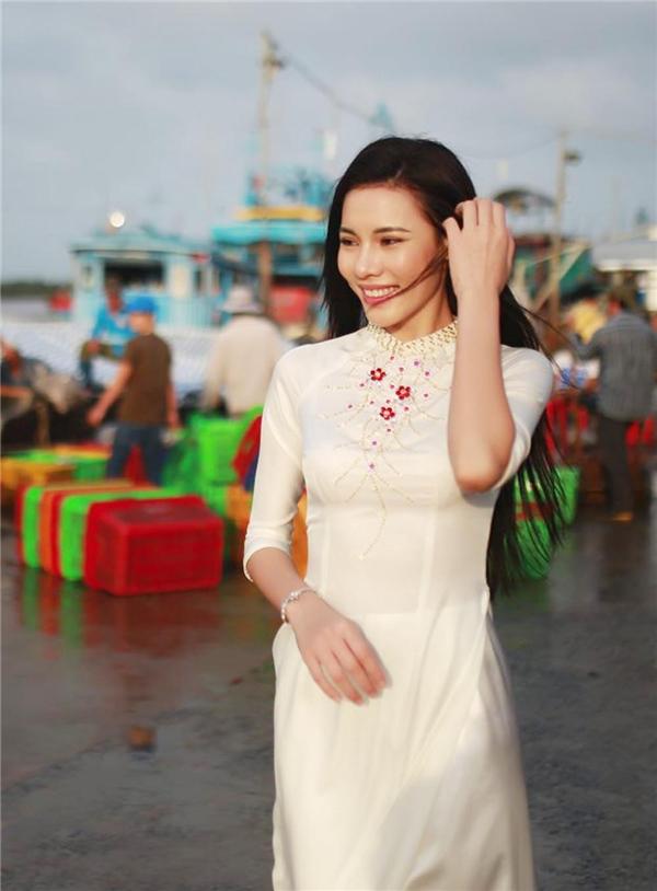 Lệ Quyên chọn áo dài trắng điểm xuyết hoa đỏ của nhà thiết kế Thuận Việt trong chuyến về thăm quê sau khi đăng quang.