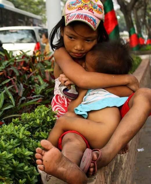 Hai chị em ôm nhau co ro trên một góc phố nhỏ, quần áo không đủ mặc, dép cũng không trọn vẹn lấy một đôi. Giấc ngủ của các em liệu có được no tròn? (Ảnh: Internet)