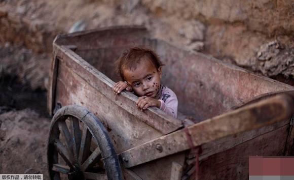 """Đứa trẻ lạc lõng, lọt thỏm trong chiếc xe gỗ với ánh mắt thất thần mặc cho ruồi bu đầy má. """"Ba mẹ đang ở đâu?"""".(Ảnh: Internet)"""